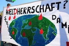 "Plakat ""W(G)eldherrschaft"" mit blutiger Weltkarte. Demo gegen TTIP in Berlin. Foto: Helga Karl, 10.Oktober 2015"