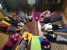un groupe de stagiaires allongés sur des tapis méditant lors d'un stage bien être organisé par Juliette ADDESSO naturopathe au gite de la Gorre en Arcéche