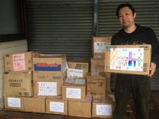 益城町に届いた物資とボランティアを行う万江さん
