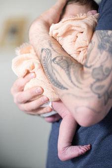 Newborn im Arm vom Papa mit tätowiertem Arm fotografiert von der Familien Fotografin Monkeyjolie in Szene gesetzt