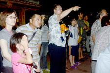 南十字星の出現に歓声を上げる参加者、中央が通事代表理事=石垣港新港地区(人工島)、サザンゲート緑地公園。30日午後8時半