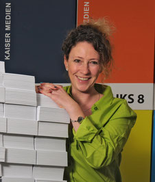Bild von Nicole Schwenk, in einer grünen Bluse vor bunten HKS Tafeln.