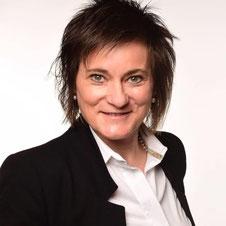 Portrait von Renate Schulz, Managerin, Kurzhaarfrisur, Blaser und Bluse, verschmitztes Lächeln