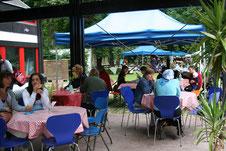 Foto einer Sonntagsöffnung - Menschen sitzen an Tischen, trinken Kaffee, plaudern.