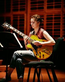Pablo Ruiz spielt sitzend mit einem Schüler Gitarre.