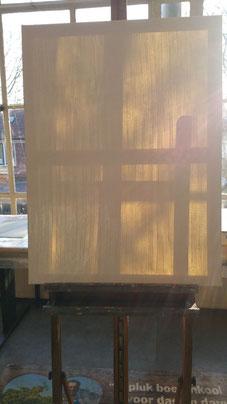 Een wit doek op een ezel, klaar om beschilderd te worden. De zon schijnt er van achter op en toont de schaduwen van de ezel door het witte doek heen.