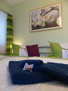 Doppelbett im Schlafzimmer mit Handtüchern und Begrüßungs-Schokolade