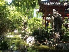 Un héron au bord d'une petite rivière et une pagode de l'autre côté de la rive