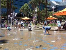 Des enfants jouent dans les jet d'eau aménagés pour se rafraîchir