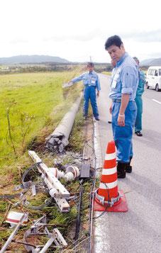 倒壊した電柱を視察する内閣府の松本政務官=30日午後、石垣市宮良