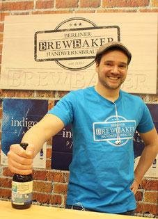 Der Berliner Braumeister Michael Schwab lachend mit Bierflasche Berliner Pils. Berlinhalle IGW. Foto: Helga Karl