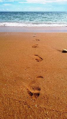 Foto von einem Strand mit Fußspuren, die aus dem Wasser kommen.