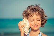 Kind lauscht in eine Muschel