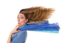 Frau mit wehenden langen Haaren im Gegenwind