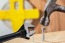 Schraubenschlüssen mit Nagel und Hammer mit Schraube