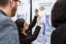 Une représentante de la Banque du Canada montre à différencier un vrai billet d'un faux à deux participants au Congrès Quartier des Affaires du Québec CQAQ de Laval photo prise par Marie Deschene photographe pour Pakolla