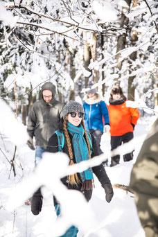 Photo d'une équipe qui fait une randonnée en raquettes en forêt pendant l'hiver durant un team-building dans les cantons de l'Est au Québec pour Évasions Canadiana par Marie Deschene photographe pour Pakolla