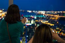 Deux participantes prennent des photos de nuit depuis le Sommet de la Place Ville Marie pendant une soirée organisée par Tourisme Montréal pour promouvoir la ville comme destination touristique photo prise par Marie Deschene photographe pour Pakolla