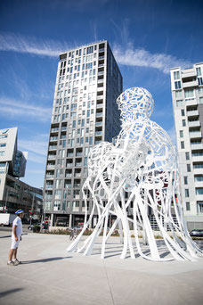 A citizen admires the sculpture Source by Jaume Plensa, 2017 in downtown Montreal photo taken by Marie Deschene photographer for Tourisme Montréal