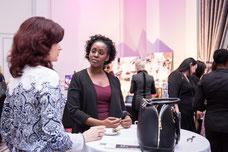 Deux femmes d'affaires discutent dans le salon des exposantes pendant la journée internationale de la femme événement organisé par Réseau des Femmes d'affaires du Québec RFAQ à Laval photo prise par Marie Deschene photographe pour Pakolla