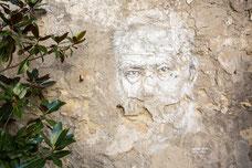 Photo d'une murale du visage d'un vieil homme sur un mur décrépit en France prise par Marie Deschene photographe pour Pakolla