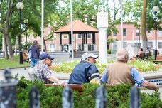Trois résidents discutent dans un parc du Quartier Le Plateau-Mont-Royal pendant l'été à Montréal photo prise par Marie Deschene photographe pour Tourisme Montréal