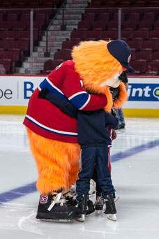 Group of children give a hug to Youppi the mascot of the Canadiens Tourism Montreal at the Bell Center in Montreal taken by Marie Deschene photographer for Pakolla