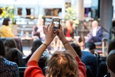 Une personne prend une photo avec son téléphone intelligent pendant une discussion à propos des congés parentaux en Suède versus au Canada pendant le Festival FIKAS de 2019 à la Place des Arts de Montréal photo prise par Marie Deschene photographe