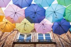 Photo d'une fenêtre d'un immeuble en colombage avec une oeuvre d'art de rue de parapluies multicolores en France prise par Marie Deschene photographe pour Pakolla