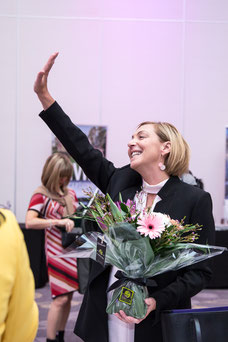 A host receives flowers during International Women's Day organized by the Réseau des Femmes d'Affaires du Québec (RFAQ) in Laval photo by Marie Deschene photographer for Pakolla
