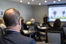 Un homme de dos écoute une conférence pendant le Congrès Quartier des affaires du Québec CQAQ à Laval photo par Marie Deschene pour Pakolla