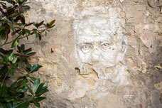 Photo of a mural of the face of an old man on a decrepit wall in France taken by Marie Deschene photographer for Pakolla