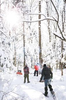 Photo d'une équipe qui fait une randonnée en raquettes en hiver pendant un team-building dans les cantons de l'Est au Québec pour Évasions Canadiana par Marie Deschene Pakolla