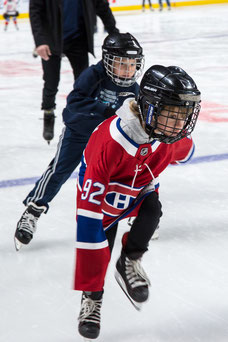 Two children race in ice skates during a team building day of Tourism Montreal at the Bell Center in Montreal photo taken by Marie Deschene photographer for Pakolla