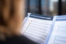 Photo d'une participante lisant la programmation du Congrès Quartier des Affaires du Québec à Laval prise par Marie Deschene