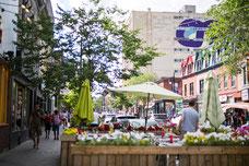 Terrasse d'un restaurant avec vue sur une murale sur La Main dans le Quartier Le Plateau-Mont-Royal pendant l'été à Montréal photo prise par Marie Deschene photographe pour Tourisme Montréal