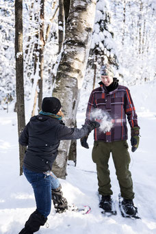 Photo of two colleagues having a snowball fight in winter during a team-building in the Eastern Townships in Quebec for Évasions Canadiana by Marie Deschene photographer for Pakolla