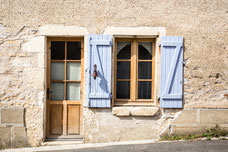 Porte d'entrée et fenêtre en bois d'une maison avec volets bleus dans un village de France Europe photo par Marie Deschene photographe Pakolla