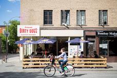 Femme sur un vélo qui passe devant la terrasse du Dirty Dogs sur Saint-Laurent dans le Quartier Le Plateau-Mont-Royal pendant l'été à Montréal photo prise par Marie Deschene photographe pour Tourisme Montréal