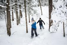 Course en raquettes en forêt par deux collègues pendant l'hiver québécois durant une journée de consolidation d'équipe dans les cantons de l'Est pour Évasions Canadiana par Marie Deschene photographe pour Pakolla