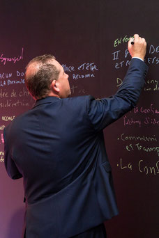 A participant writes an idea on a board that he has during the annual conference of the Association of Directors and general managers of the Desjardins ADGC caisses at the Fairmont Mont-Tremblant taken by Marie Deschene photographer at Pakolla