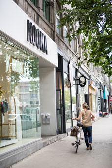 Femme pousse son vélo devant les boutiques sur Saint-Laurent dans le Quartier Le Plateau-Mont-Royal pendant l'été à Montréal photo prise par Marie Deschene photographe pour Tourisme Montréal