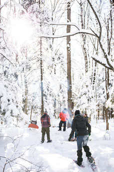 Photo of a team doing a snowshoe hike in hi worm during a team-building in the eastern cantons of Quebec for Évasions Canadiana by Marie Deschene photographer for Pakolla
