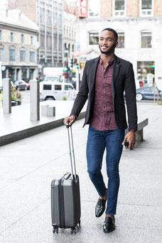Portrait corporatif homme d'affaires noir barbu avec valise dans les rues de Montréal photo par Marie Deschene photographe pour Pakolla