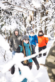 Photo d'une jeune femme qui fait une randonnée en raquettes en hiver dans le bois pendant un team-building dans les cantons de l'Est au Québec pour Évasions Canadiana par Marie Deschene photographe pour Pakolla