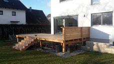 Terrasse aus Holz mit Treppenabgang und Geländer
