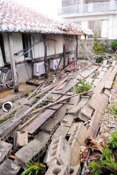 隣地のブロック塀が倒壊し、慶田城さん宅の庭が押しつぶされた=24日午前8時ごろ、石垣市登野城