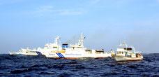 一般人が乗り込んだ漁船(右端)、日本の巡視船、中国公船(左端)が入り乱れる尖閣海域(昨年6月)=仲間均市議提供