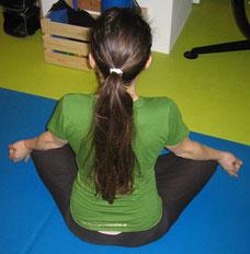 Frau im Meditationssitz in Rückenansicht