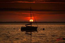 Voilier au mouillage, le soleil se couche dans une dominante rouge